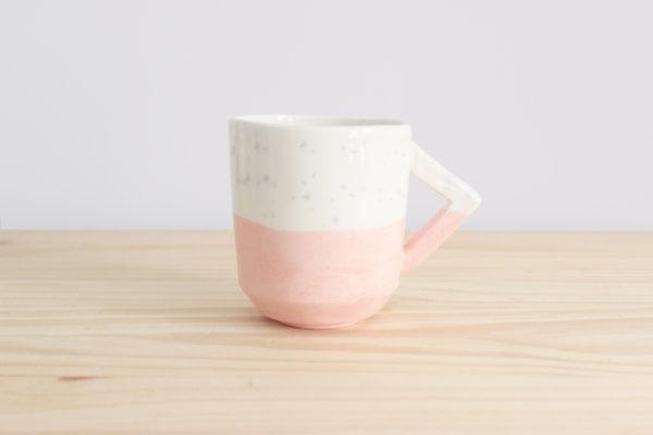 Taza realizada a mano con diseño de asa rectangular en loza blanca en tonos rosas y azules
