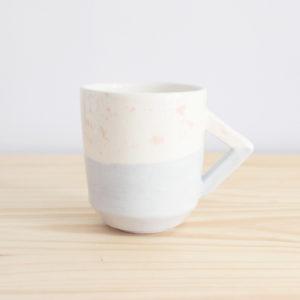 Taza de diseño realizada artesanalmente en loza blanca con decoración en rosa y azul y detalle de asa rectangular