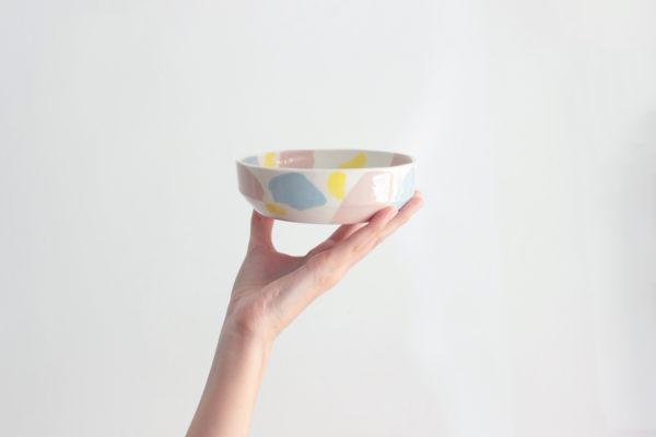 Bol hecho a mano para aperitivos en loza blanca y líneas rectas en azul, rosa y amarillo