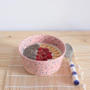 Bol artesanal rosa con manchas azules utilizado para yogur y fruta